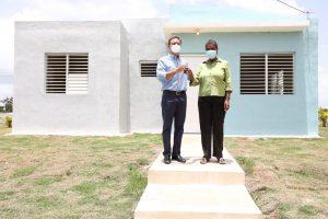 El procurador Jean Rodríguez mientras hace entrega de las llaves de una de las viviendas a la señora María Altagracia Rosario (Milagros)